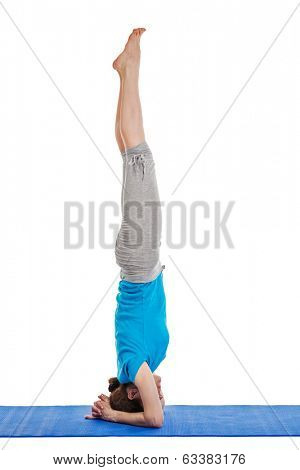 Yoga - young beautiful woman yoga instructor doing headstand (sirsasana) asana exercise isolated on white background