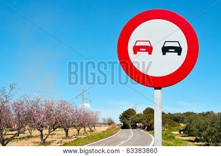 no overtaking sign in a secondary road with almond trees in full bloom