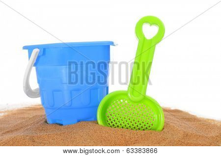 toy shovel and beach pail on the sand on a white background