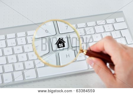 Looking At House Key Through Magnifying Glass
