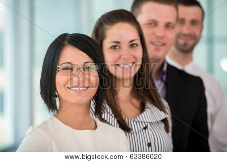 Happy female manager standing with coworkers in a row