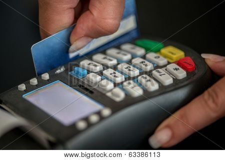 Hands swiping magnetic card on pos terminal