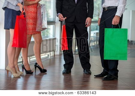 Legs of four people in modern clothes with paper bags