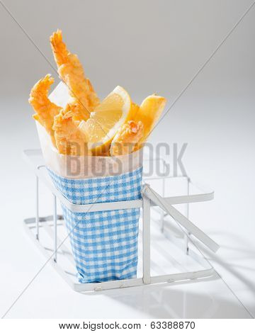 Single serving of Tempura prawns and fries with lemon slice garnish wrapped in blue check napkin