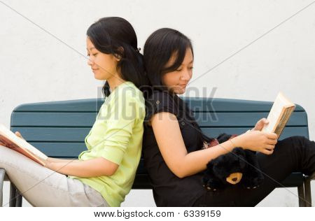 Two Young Woman Enjoy Reading Together