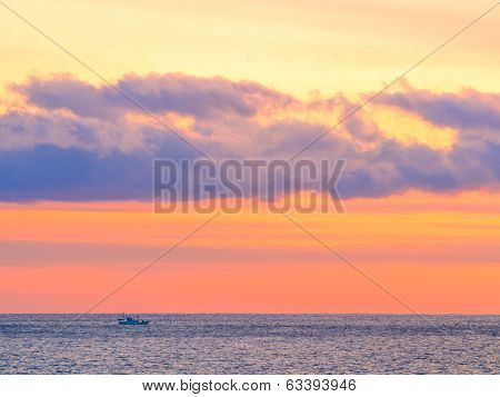 Sea sunset glow with clouds and sailing fishing boat
