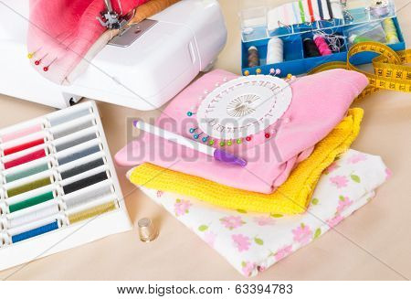 Sewing machine with colorful fabrics, threads, thimble and other sewing accesories.