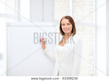business and education concept - smiling businesswoman writing on flipchart