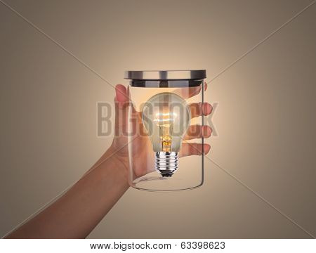 Hand hold glass jar with bulb inside isolated on white background