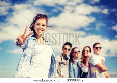summer holidays and teenage concept - teenage girl in sunglasses hanging out with friends outside and showing thumbs up