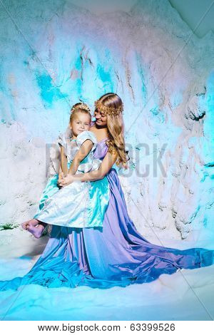 Little girl with mother in princess dress on a background of a winter fairy tale. Baby and mom snow queen. Smiling child and mum snowy kingdom. Kid in in carnival costume.