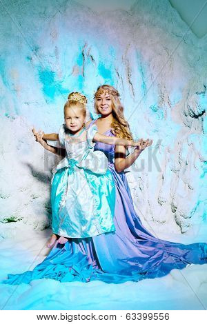 Little girl with mother in princess dress on a background of a winter fairy tale. Baby and mom snow queen. Sweet smiling child and mum snowy kingdom. Kid in in carnival costume.