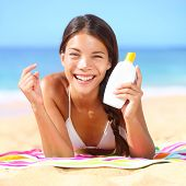 Sunscreen woman applying suntan lotion showing bottle. Beautiful smiling happy asian woman with sunt