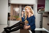 picture of woman red blouse  - Attractive sexy blonde female with bright blue blouse and black stockings posing smiling holding a glass with red wine - JPG