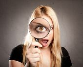 woman looking at camera through magnifying glass on gray background