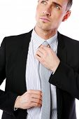 Confident businessman straightening his tie over white background