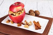 Stuffed apple with nuts and cinnamon on plate on wooden background