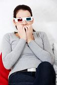 Sceared woman in 3d glasses is watching movie.
