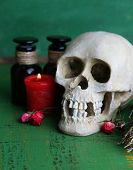 Composition with skull, and , magic potions, candle  on color wooden background