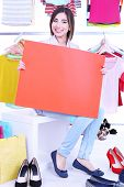 Beautiful young woman holding blank poster in shop