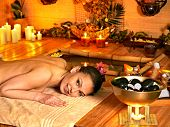 Woman getting stone therapy massage in bamboo spa.