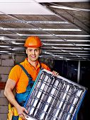 image of suspenders  - Man in builder uniform installing suspended ceiling - JPG