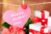 Happy Mothers Day message written on paper heart with flowers on brown background