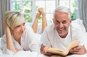 Happy mature couple lying and reading book in bed at home