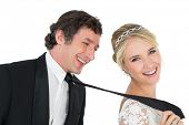 Portrait of attractive bride pulling tie of groom over white background