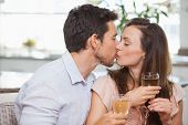 Close-up of a loving young couple with wine glasses kissing at home