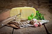 Cheese, mushrooms and aromatic herbs on old wooden background