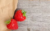 Ripe strawberries over wooden table background and paper with copy space