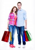 Full portrait of beautiful young happy couple with colored shopping bags - isolated on white.