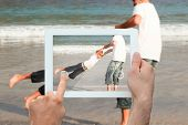 Hand holding tablet pc showing father and son having fun at the beach