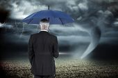 Businessman holding umbrella against stormy sky with tornado over field