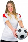 Pretty football fan in white smiling on white background