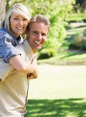 Portrait of smiling couple enjoying piggyback ride in park