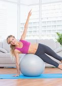 Happy fit blonde doing side plank with exercise ball at home in the living room