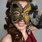 Young woman in carnival mask on gray background.