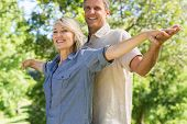 Portrait of happy couple standing arms outstretched in park