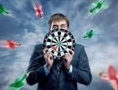 Businessman holding darts board in his hands