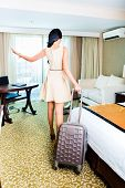 Rear view of woman pulling suitcase in hotel room
