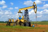 picture of nonrenewable  - Oilfield Pump Jack with a bright blue sky and clouds - JPG