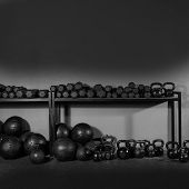 stock photo of barbell  - Kettlebells dumbbells and weighted slam balls weight training equipment at gym - JPG