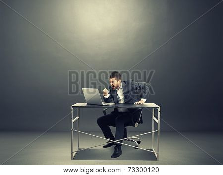 agressive businessman looking at laptop, screaming and showing fist. photo in the dark room with empty copyspace