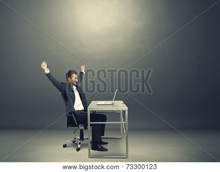 successful businessman raising hands up, looking at laptop and laughing. photo in the dark room with empty copyspace