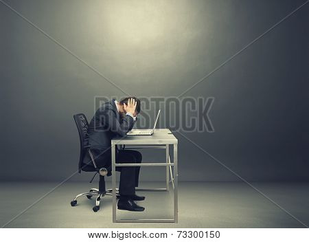 depressed businessman sitting at the table with laptop and covering his head in the dark room