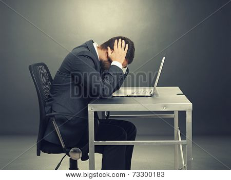 depressed businessman sitting at the table with laptop and covering his head over dark background