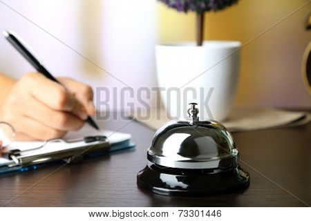 Female hand  writing in Hotel guest book on reception desk, on bright background