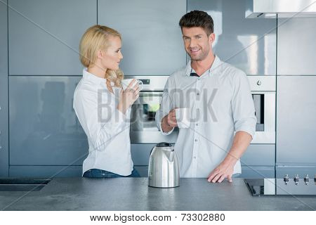 Attractive couple enjoying their early morning coffee standing together in the kitchen chatting with their mugs in their hands